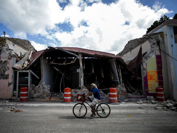 A cyclist rides past a destroyed building in Guanica, Puerto Rico. The island was hit by a series of earthquakes over the past couple of weeks, leading to a state of emergency, power outages and millions of dollars of damage.