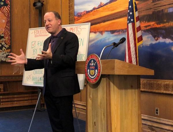 Gov. Jared Polis talks to reporters at the state Capitol.