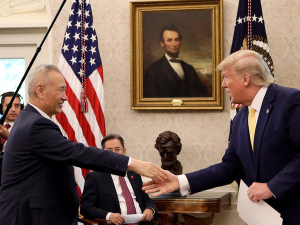 """President Trump shakes hands with Chinese Vice Premier Liu He at the White House after announcing a """"phase one"""" trade agreement with China on Oct. 11, 2019. The two leaders are meeting again in Washington on Wednesday to sign the deal."""