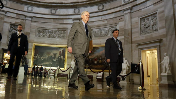 Senate Majority Leader Mitch McConnell, R-Ky., center, walks through the rotunda at the Capitol on Wednesday.