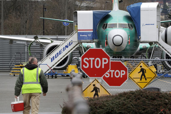 In this Monday, Dec. 16, 2019, file photo, a Boeing worker walks in view of a 737 MAX jet in Renton, Wash. (Elaine Thompson, File/AP)