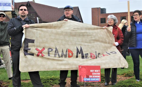Protesters last year targeted Senate Majority Leader Jim Denning for blocking Medicaid expansion. Now he and Gov. Laura Kelly have settled on a compromise.