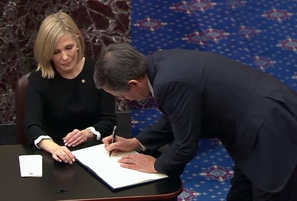 Montana U.S. Sen. Steve Daines signs the oath book as he's sworn in for the impeachment trial of President Donald Trump on Jan. 16, 2020.