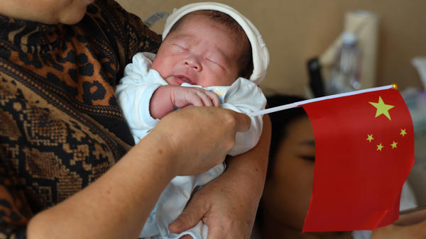 A woman carries a baby born on China's National Day, Oct. 1, 2019, at a hospital in Chengdu, China. Experts say that once-strict government restrictions on births is likely to place a burden on the country's economy.