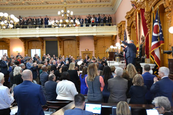 Speaker Larry Householder (R-Glenford), along with Gov. Mike DeWine and Senate President Larry Obhof (R-Medina), stand at the dais in the Ohio House and wave at the 2019 State of the State speech.