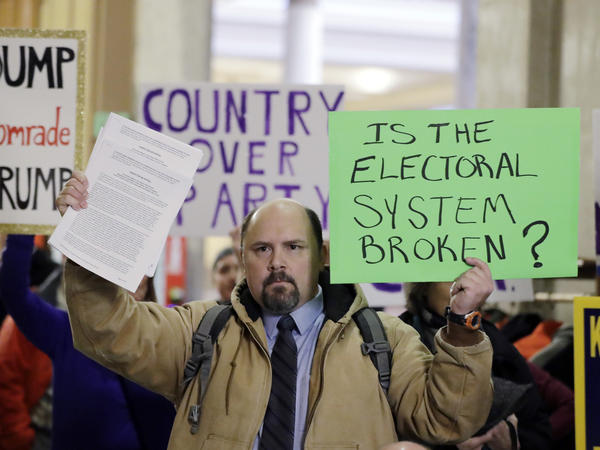 Brock Ervin holds a sign outside the Indiana House chamber before the 11 representatives of the Electoral College gathered on Dec. 19, 2016, in Indianapolis. The U.S. Supreme Court has agreed to hear two cases challenging state attempts to penalize Electoral College delegates who fail to vote for the presidential candidate they were pledged to support.