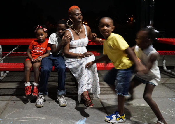 In this file photo, Dierdre Wortham relaxes while members of her family play around her. Her son Aiden (second from left) had to forgo treatment after the state removed them from Missouri's Medicaid program.