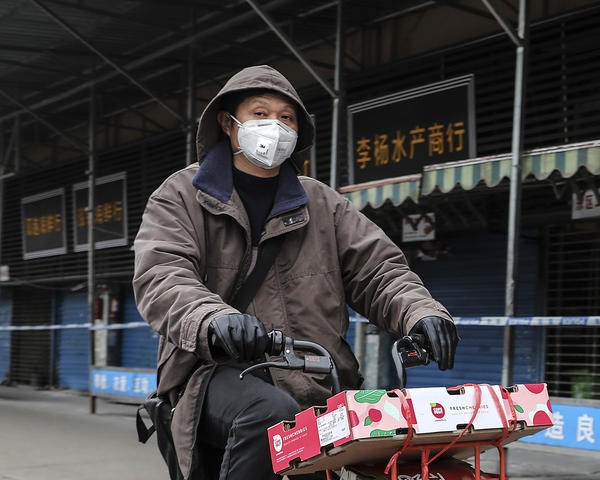 A man rides past the Huanan Seafood Wholesale Market in Wuhan, China, which was closed after being linked to cases of a newly discovered coronavirus.