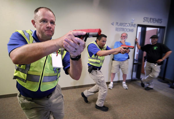 Police officers David Riggall, left, and Nick Guadarrama, center, demonstrate how to clear a hallway intersection during a security training session at Fellowship of the Parks campus in Haslet.