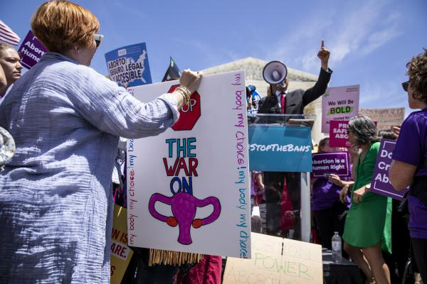 A pro-choice activist holds a sign as Sen. Cory Booker, a Democrat from New Jersey, speaks during a rally in front of the U.S. Supreme Court in May. A recent Gallup poll found that more Americans want less strict abortion laws.