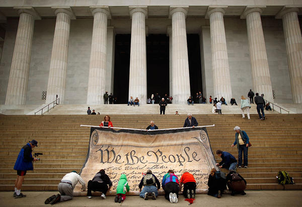 Volunteers help roll up a giant banner printed with the Preamble to the United States Constitution during a demonstration against the Supreme Court's Citizens United ruling at the Lincoln Memorial on the National Mall October 20, 2010 in Washington, DC. The rally at the memorial was organized by brothers Laird and Robin Monahan who spent the last five months walking from San Francisco, California, to Washington to protest the court decision, which overturned the provision of the McCain-Feingold law barring corporations and unions from paying for political ads made independently of candidate campaigns.  (Chip Somodevilla/Getty Images)