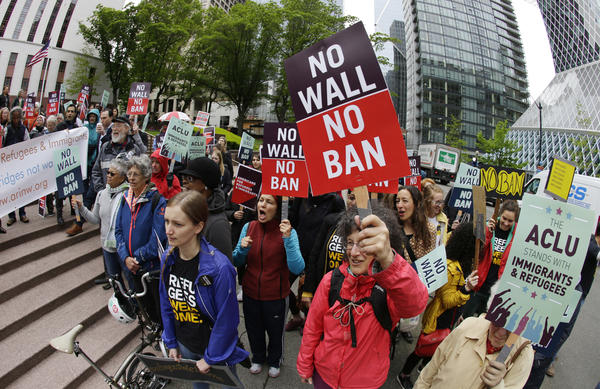 In this May 15, 2017 file photo, protesters wave signs and chant during a demonstration against President Donald Trump's revised travel ban, outside a federal courthouse in Seattle.