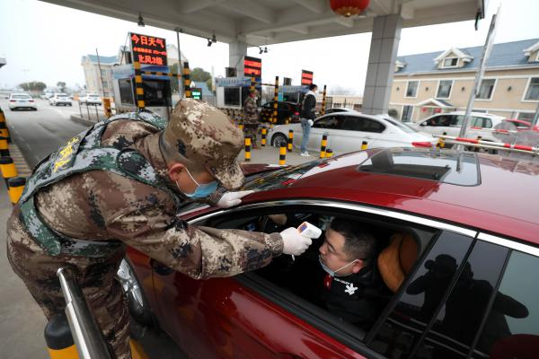 A militia member checks the body temperature of a driver at an expressway toll gate in Wuhan, China.