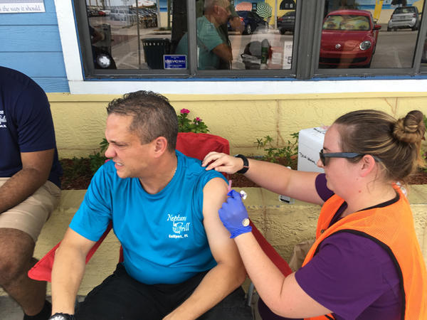 A nurse with the health department in Pinellas County delivered a hepatitis A shot to a restaurant employee in Gulfport this summer, part of the county's efforts to combat the virus. JULIO OCHOA/WUSF PUBLIC MEDIA