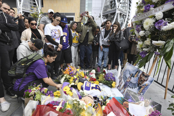 Valerie Samano, left, places flowers at a memorial near the Staples Center in Los Angeles, after the death of Laker legend Kobe Bryant on Sunday.