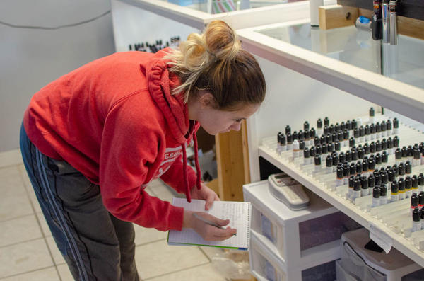 Faith White, an employee of Great Alternatives Vape Shop in suburban Des Moines, takes inventory of the store's vaping flavors.