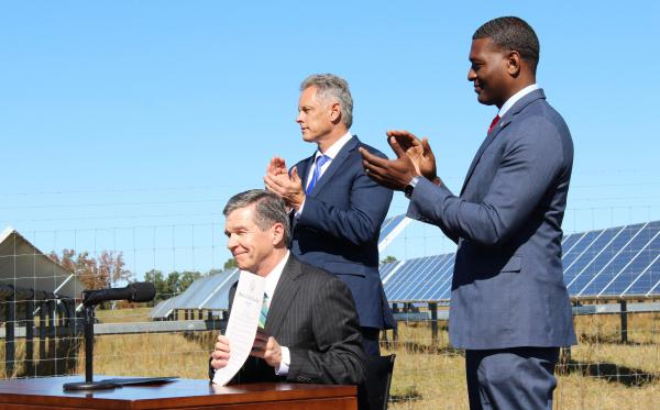 Gov. Roy Cooper (seated) set state climate goals in Executive Order 80 in 2018 at SAS Institute's solar farm in Cary.  With him were DEQ Secretary Michael Regan (right) and SAS executive Jerry Williams.