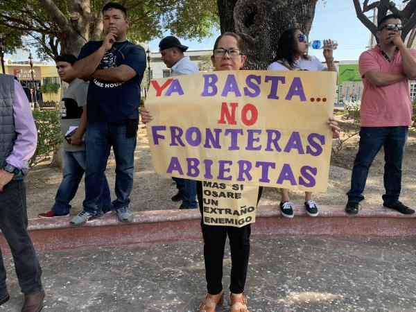 A protestor holds a sign during a protest of the growing tent encampent in Matamoros, Mexico on January 26th, 2020.