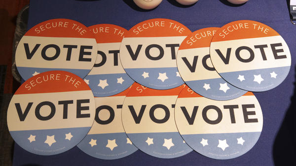 "Computer mouse pads with ""Secure the Vote"" logos on them sit on a vendor's table at an election officials conference in 2018."
