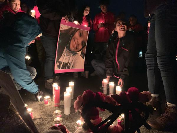People gather around candles and a picture of Selena Not Afraid at a nighttime vigil Jan. 21, 2020.