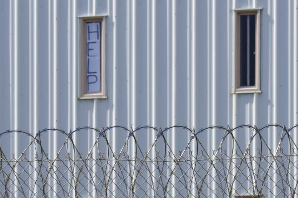 """A sign placed in the window of an inmate's cell calls for """"HELP"""" during a visit by state officials last year. Holman Correctional Facility in Atmore, Ala., long criticized for its conditions, will be largely decommissioned."""