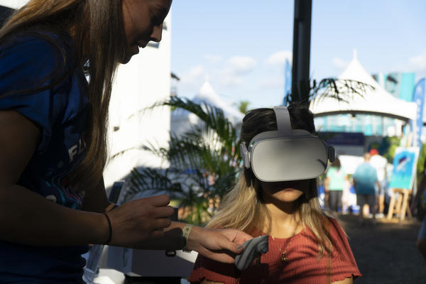 Caroline Dennison guides Keylin Colindres to virtually dive underwater and see South Florida reefs at a booth by Mote Marine Laboratory, a marine research nonprofit. This was one of several environmental installations during a Super Bowl Miami event.