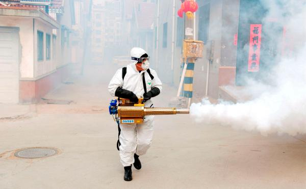 A worker in a protective suit uses a large fogger to disinfect outdoor areas in a village in Qingdao, Shandong province, as the deadly new coronavirus continues to spread in China.