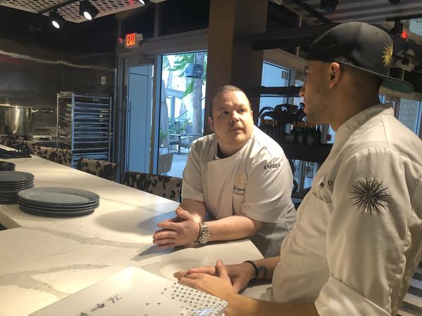 Kansas City native Brad Kilgore, now a chef in Miami, speaks to his sous chef, Gionathon Rivera, before opening his midtown Miami restaurant Ember earlier this week. Kilgore is helping to organize a Super Bowl block party for Chiefs fans.