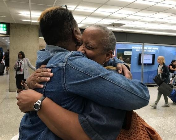 Wanda Tucker, left, and reporter Deborah Barfield Berry hug at the Dulles International Airport after returning on separate flights from a 10-day trip to Angola, from which they traced their ancestors.