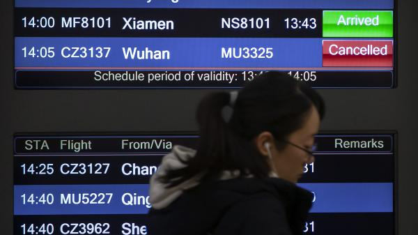 A traveler walks past a display board showing a canceled flight from Wuhan at Beijing Capital International Airport on Thursday. China closed off the city of more than 11 million in an unprecedented effort to try to contain a deadly new viral illness that has sickened hundreds and spread to other cities and countries during the Lunar New Year travel rush.