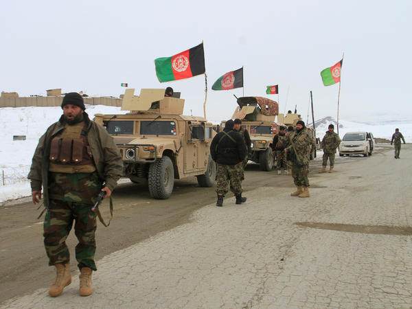 Afghan service members head toward the site of the plane crash Monday in the eastern Afghan province of Ghazni.
