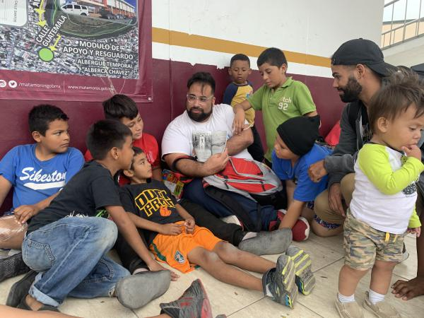 Ray Rodriguez, center, reads a book to children at the Sidewalk School in Matamoros, Mexico.