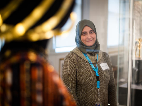 """The University of Pennsylvania Museum of Archaeology and Anthropology — known as The Penn Museum — has hired refugees and immigrants from the Middle East, Africa and Central America as part of their """"Global Guides"""" program. Moumena Saradar, who is originally from Syria, stands next to the wedding jewelry and headdress of Queen Puabi, her favorite part of the Middle East gallery."""