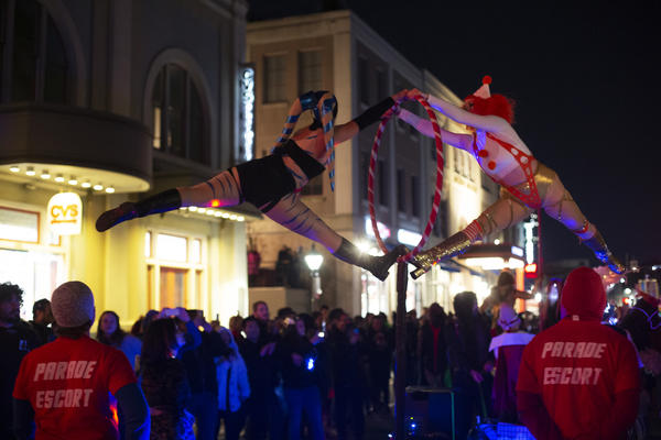 Members of the Aerial Space Squad sub-krewe perform acrobatics above the crowd on a pole and hoops.