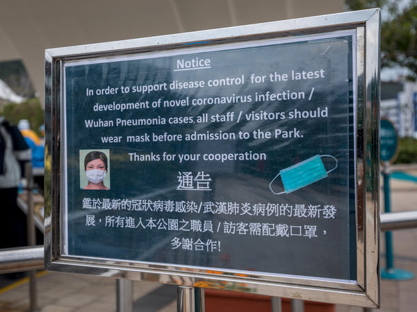 A notice advising all staff and visitors to wear protective masks stands outside the closed Ocean Park in Hong Kong, on Monday.