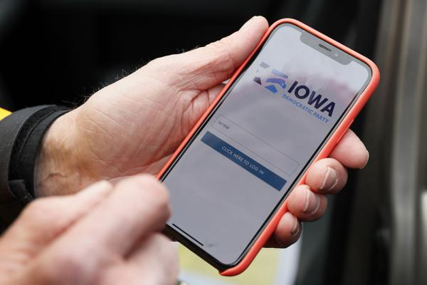 Precinct captain Carl Voss holds his iPhone that shows the Iowa Democratic Party's caucus reporting app Tuesday, Feb. 4, 2020, in Des Moines, Iowa. (Charlie Neibergall/AP Photo)