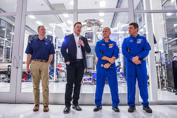 SpaceX founder Elon Musk addresses the media alongside NASA Administrator Jim Bridenstine, and astronauts Doug Hurley and Bob Behnken, during a press conference announcing new developments of the Crew Dragon reusable spacecraft, at SpaceX headquarters in Hawthorne, California on October 10, 2019. (Philip Pacheco / AFP)