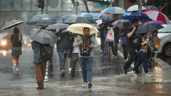 People commute to work through heavy rain in Sydney on Friday. Severe weather brought warnings of floods and landslides along much of the New South Wales coast after months of concerns over wildfires.