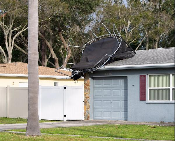 A trampoline lands on top of a house after a confirmed tornado touched down in Pinellas Park. JONAH HINEBAUGH/WUSF PUBLIC MEDIA