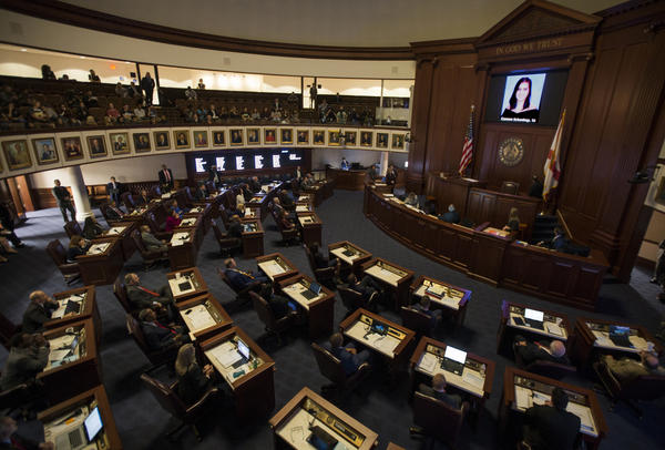 In this Feb. 21, 2018, file photo, the Florida Senate chamber is darkened while a slideshow shows each person killed in a shooting at Marjory Stoneman Douglas High School, at the state Capitol in Tallahassee, Fla.