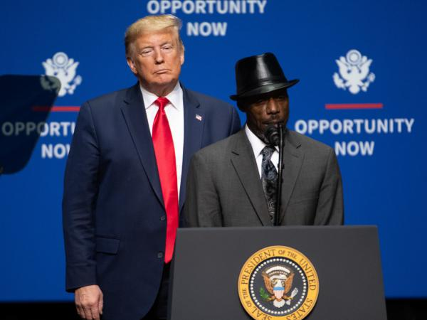 President Trump looks on as Tony Rankins, who works in a so-called Opportunity Zone, addresses a crowd during a speech Friday in Charlotte, N.C., aimed squarely at appealing to African American voters.