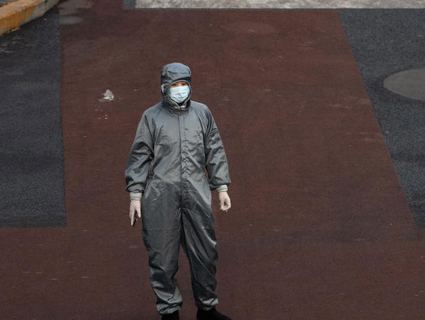 A Chinese woman wears a protective suit and mask as she waits to cross the intersection of a nearly empty Beijing on Saturday.