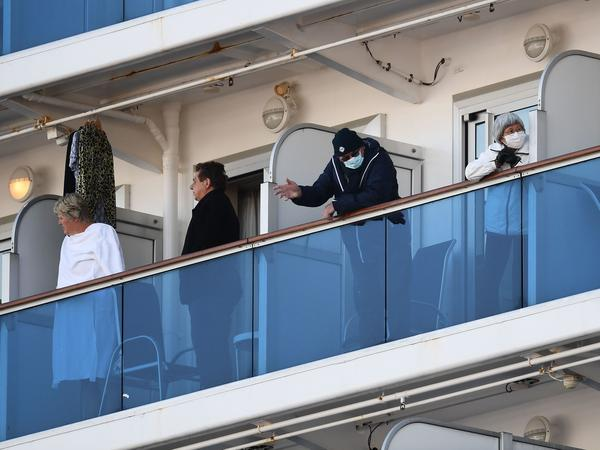 The quarantined Diamond Princess cruise ship has 65 new cases of coronavirus, Japanese officials announced Monday. Here, passengers with ocean-facing rooms stand on their balconies as the ship sits at the Daikoku Pier Cruise Terminal in Yokohama, Japan.