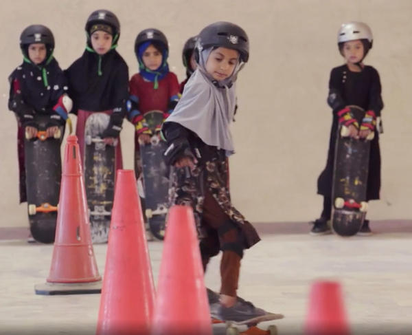 """Students wearing headscarves and helmets learn to navigate traffic cones in a scene from the Oscar-winning documentary, """"Learning to Skateboard in a Warzone (If You're a Girl)."""""""