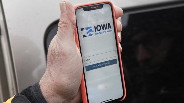 Precinct captain Carl Voss of Des Moines displays the Iowa Democratic Party caucus reporting app on his phone outside of the Iowa Democratic Party headquarters.
