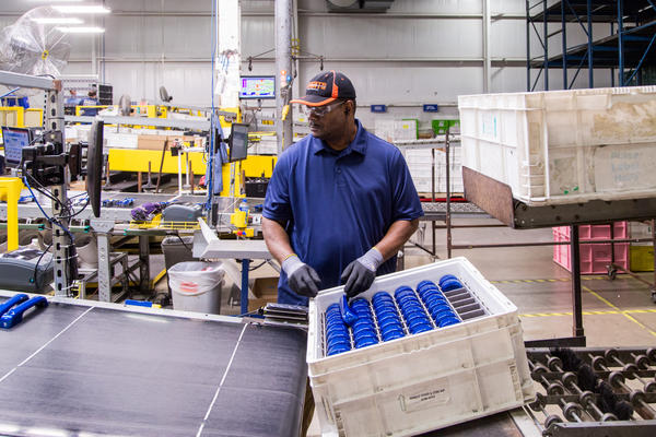 A worker at ADAC Automotive handles auto parts at their plant in Muskegon. ADAC Automotive works with factories in China and has been dealing with the impacts of the coronavirus.