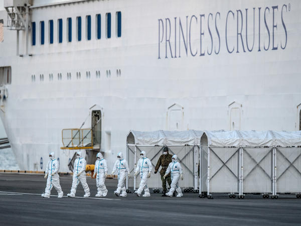 Emergency workers in protective clothing exit the quarantined Diamond Princess cruise ship where it was being resupplied Monday off Yokohama, Japan.