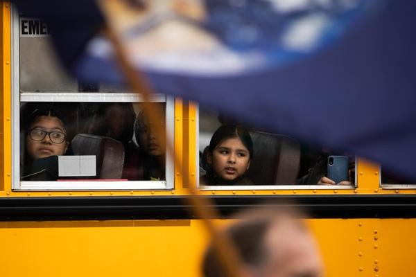 <p>A school bus of children visiting the Capitol drives by the crowd of people attending a rally for climate action in Salem, Ore., Feb. 11, 2020.</p>