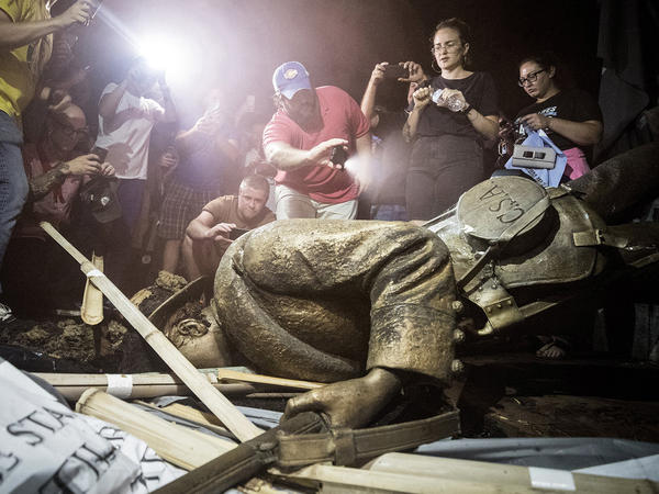 Demonstrators and spectators gather around the toppled Confederate statue known as Silent Sam in August 2018 at UNC-Chapel Hill in North Carolina. A judge has overturned a settlement that the UNC System made with the Sons of Confederate Veterans.