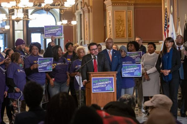 State Sen. Omar Aquino speaks to a rally of supporters for a bill changing the state's formula for distributing Medicaid funding to hospitals. At immediate right, state Rep. Emanuel Chris Welch looks on.